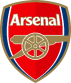"In 1888, just two years after the formation of the Club, Arsenal, then called Royal Arsenal, adopted its first crest. This was based largely on the coat of arms of the Borough of Woolwich. The Club was based in the Borough from its formation until 1913, playing at Plumstead Common; Sportsman Ground; Manor Ground; Invicta Ground and the Manor Ground again before heading across London to Highbury, Islington prior to the move to Emirates Stadium. The original badge comprised three columns, which, although they look like chimneys, are in actual fact cannons. The significance of the cannons to the Borough of Woolwich derives from the long military history surrounding the area. The Royal Arsenal, Royal Artillery Regiment and various military hospitals – which still dot the landscape today – were all prominent in the Borough. The cannons on the original crest were obviously a reference to the military influence in Woolwich and despite the Club's ties with the area being cut 89 years ago, the cannon theme has developed throughout the years and has remained prominent on the Gunners different crests down the years, including the new design. In the early days the crest was not as significant a part of a football club's identity as it is today. Shirts remained plain, unless commemorating a significant match, an FA Cup Final for example, and the crest was generally reserved for official headed stationery, matchday programmes and handbooks. Following Arsenal's move north to Highbury in 1913, it wasn't immediately apparent that the Club would embrace the Woolwich Arsenal legacy and keep the cannon as a recognisable motif. The Club soon became just 'Arsenal', the Great War affected football for four seasons and recommencing in 1919/20 'normal' football took some time to settle. During all of this period there was no sign of a crest as such but, in the first matchday programme of the 1922/23 season, when the Gunners played Burnley, a new club crest was revealed – a fearsome looking cannon – that would have sat proudly in the Royal Arsenal of Woolwich. As can be seen the vertical cannons have gone with the new design featuring a single eastward pointing cannon. Whoever designed this robust looking weapon saw his handiwork used by the Club for just three seasons however, and for the start of the 1925/26 season, the Gunners changed to a westward pointing, narrower cannon with the legend 'The Gunners' remaining next to it. The derivation of the narrower cannon has never been officially confirmed, but the cannons on the crest of the Royal Arsenal Gatehouse in Woolwich are uncannily similar to that used as the Gunners' symbol. This cannon crest remained prominent in the Arsenal matchday programme and other publications for 17 seasons. It changed slightly through the years with the wording eventually disappearing, but despite being usurped by the Victoria Concordia Crescit crest in 1949 it has remained a basic symbol of the Club ever since, featuring on official merchandise and stationary throughout the years right up until the present day. The VCC crest , which the current crest replaced, had been Arsenal's symbol since appearing in the first programme of season 1949/50. It would appear to have been in the minds of the Gunners hierarchy for at least a year prior to this. In the final matchday programme of the 1947/48 League Championship winning season, 'Marksman' (aka Harry Homer), the programme editor of the day, wrote: ""...my mind seeks an apt quotation with which to close this season which has been such a glorious one for Tom Whittaker, Joe Mercer and all connected with The Gunners. Shall we turn for once to Latin? 'Victoria Concordia Crescit'. Translation: 'Victory grows out of harmony.'"" Two seasons later and Arsenal unveiled its new crest which incorporated Marksman's Latin maxim. Tom Whittaker explained in the 1949/50 handbook (which also included the new crest) that the Club had been impressed by Marksman's motto and it had now been officially adopted by the Club. The new crest also featured 'Arsenal' in a gothic style typeface, the westward facing cannon, the Borough of Islington's coat of arms and ermine. For the next 53 years this crest remained largely unchanged (7), though at the start of the 2001/02 season it was 'cleaned up' somewhat for commercial reasons, with a solid yellow replacing the different tones of gold and Victoria Concordia Crescit written in a less ornate typeface. The Club's identity has thus evolved over the years and the decision to formulate a new crest in 2002 was two-fold. Firstly, as the VCC crest incorporated many separate elements introduced over a number of years, there was uncertainty surrounding its exact origination. Consequently, the Club was unable to copyright the crest. Secondly, it had always been one of the Club's primary objectives to embrace the future and move forward. With Emirates Stadium on the horizon and the Gunners consistently challenging for domestic and European honours, the Club believed it was the ideal time to introduce a new crest. The shirt for the 2011/12 season featured a special 125th anniversary crest design (10) combining the graphic of the first Club crest with the current version. The celebratory design features 15 laurel leaves to the left side of the Club's crest to reflect the detail on the reverse of the six pence pieces paid by 15 men to establish the Club - the laurel leaves also represent strength. The 15 oak leaves to the right of the crest acknowledge the founders who would meet in the local Royal Oak pub. Underneath the crest is one of the first recorded mottos related to the armament and battle - 'Forward' - with the anniversary dates of 1886 and 2011 either side of the heart of the shirt."